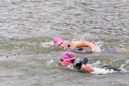 Two triathletes swim on start of the triathlon competition in Moscow River, Moscow, Russia