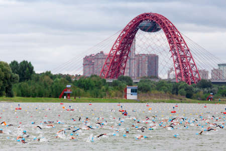Triathletes swim on start of the triathlon competition in Moscow River with cable-stayed red Jivopisny Bridge behind, Moscow, Russia