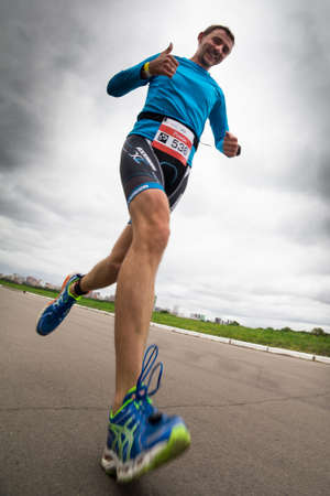 Thumbs-up triathlete runs during triathlon competition, bottom view, Moscow, Russia Editorial