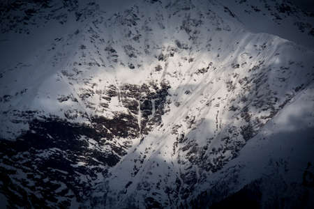 top view to Caucasian mountains covered by snow and cloud shadows Stock Photo