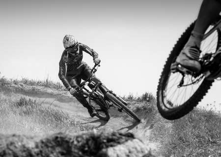Russia, Moscow - April 29, 2012: Mountainbiker rides on hill path at summerKAT 2012 competition, black and white