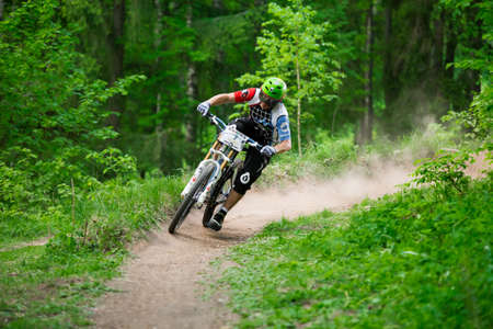 Russia, Obninsk - May 18, 2013: Mountainbiker rides through green forest at REACTOR CUP contest, Obninsk, Russia Editorial