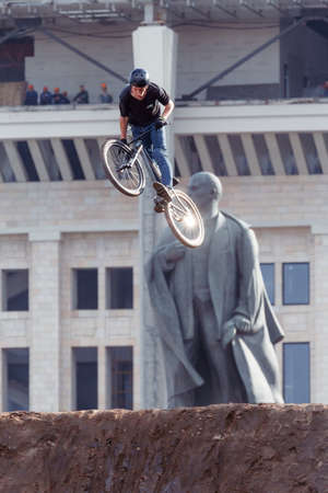 Russia, Moscow, July 23, 2016: Mountainbiker makes a stunt in front of Lenin monument at Moscow City Games contest, Luzhniki, Moscow, Russia
