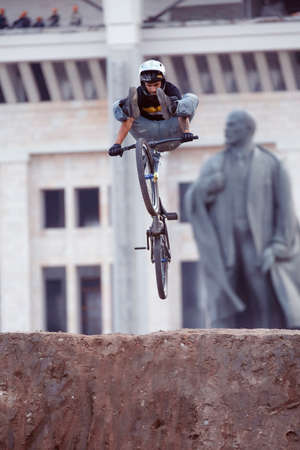 clicker: Russia, Moscow, July 23, 2016: Mountainbiker makes a heel clicker trick in front of Lenin monument at Moscow City Games contest, Luzhniki, Moscow, Russia Editorial