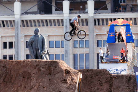 Russia, Moscow, July 23, 2016: Mountainbiker makes a trick in front of Lenin monument at Moscow City Games contest, Luzhniki, Moscow, Russia