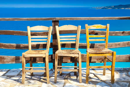 Greece romantic composition: three chairs and deep blue sea