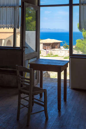 Greece romantic composition: table and chair near the window and deep blue sea behind