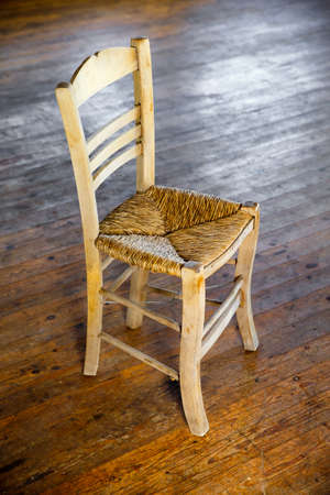 Traditional cane seat chair in the sun shadow on old wood floor Stock Photo