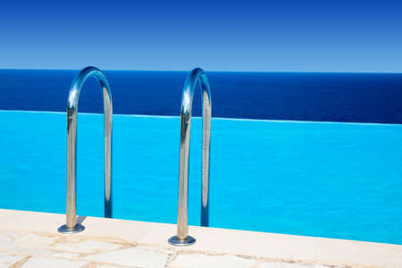 rails to luxury blue swimming pool near the sea and sunny sky above Stock Photo