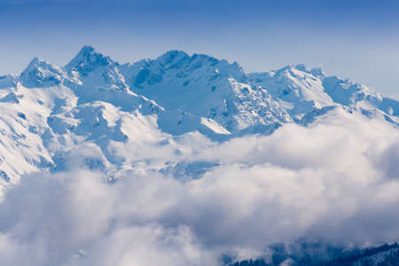 Snow mountains peaks covered by clouds on the sun Stock Photo