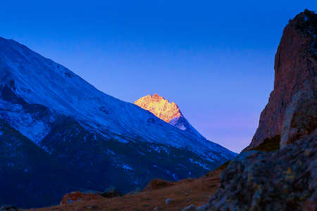 bright sunset over Caucasian mountains peaks in blue dusk