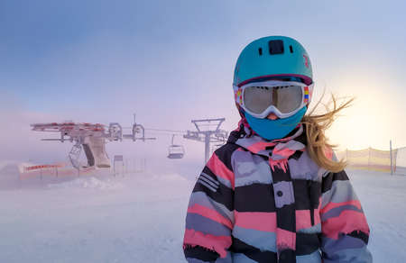 Closeup portrait of skier girl wearing mask, helmet and googles in the snowy mountains on a windy and foggy day, cableway in the background. Ski in winter season, top of snowy mountains