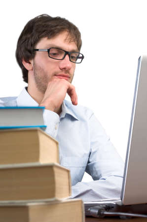 Man at a table with books working on a laptop. photo