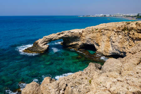 The rocky coast and the Mediterranean Sea of Cyprus. Rock in the form of an arch. Banco de Imagens