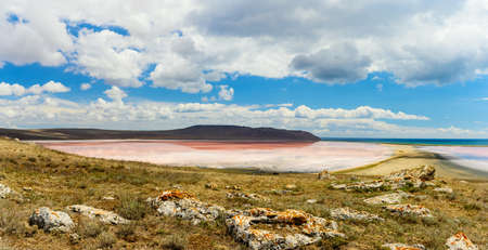 Landscape. View of a small pink lake from the mountain. In the foreground are huge old stones. above the lake blue sky with clouds.