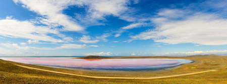 View of a small pink lake. Around the lake fields. above the lake blue sky with clouds.