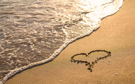A heart is drawn on the sandy beach. The sea wave washes the beach at sunset.