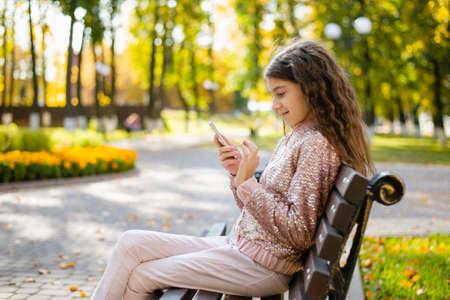 一个女孩坐一条长凳在一个秋天公园有一个电话的在她的手上。这个女孩正在玩电子游戏。