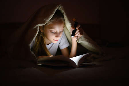A girl at night under the covers with a flashlight reads a book.