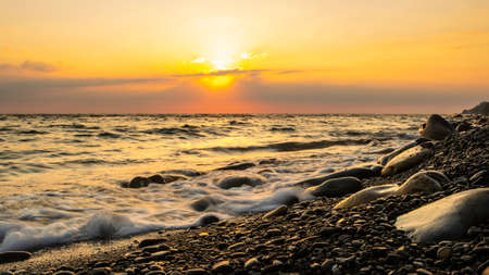 Sunset at the sea. Pebble beach and surf at sunset. Long exposure shooting. Focusing on water's edge and pebbles.