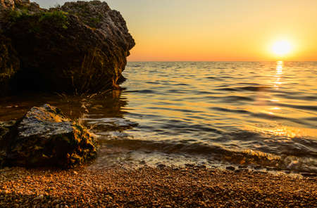 Seashore with huge stones at sunset. splashing water from the sea wave over the stone. Focusing on a nearby stone. Stok Fotoğraf