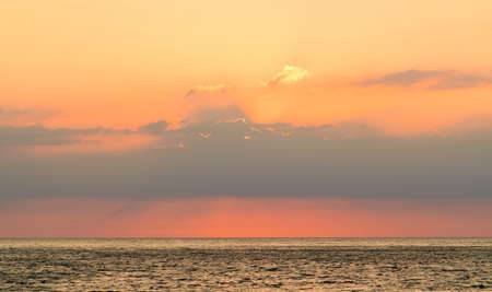 The sky is orange during sunset over the calm sea. Sunset over the sea. Stok Fotoğraf
