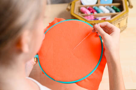 The girl is learning to embroider. The girl is holding a hoop with an orange cloth and a thread with a needle. Focusing on the hand with a needle.
