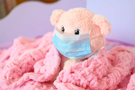 A pink teddy bear in a medical mask and a thermometer sits covered with a pink blanket. Coronovirus or flu disease concept. Focusing on the bear's eye. Stockfoto
