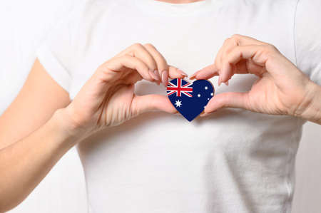 Love Australia. The girl holds a heart in the form of the flag of Australia on her chest. Australian patriotism concept