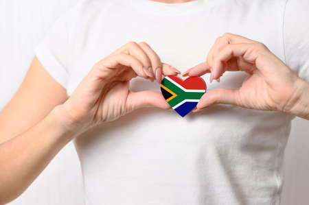 Love South Africa. The girl holds a heart in the form of the flag of South Africa on her chest. South African concept of patriotism