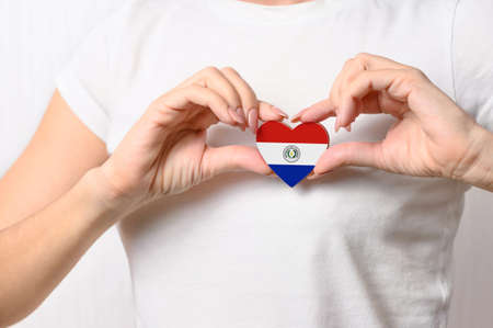 Love Paraguay. The girl holds a heart in the form of the flag of Paraguay on her chest. Paraguayan patriotism concept