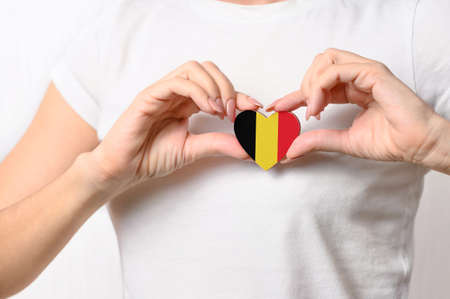 Love Belgium. The girl holds a heart in the form of the flag of Belgium on her chest. Belgian patriotism concept