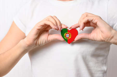 Love Portugal. The girl holds a heart in the form of the flag of Portugal on her chest. Portuguese patriotism concept