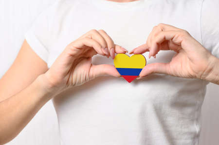 Love Colombia. The girl holds a heart in the form of the flag of Colombia on her chest. Colombian patriotism concept Banque d'images