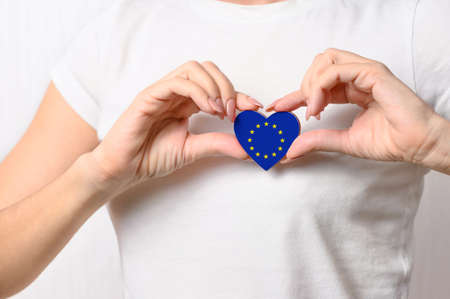 Love European Union. The girl holds a heart in the form of the flag of EU on her chest. European patriotism concept