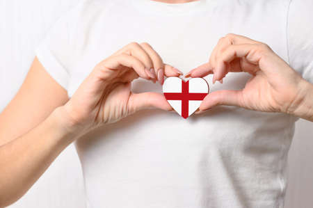 Love England. The girl holds a heart in the form of the flag of England on her chest. English patriotism concept Banque d'images