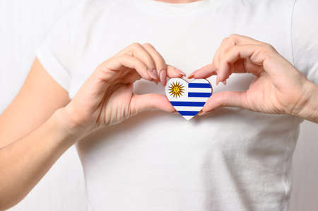 Love Uruguay. The girl holds a heart in the form of the flag of Uruguay on her chest. Uruguayan patriotism concept Banque d'images