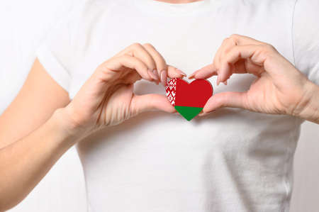 Love Belarus. The girl holds a heart in the form of the flag of Belarus on her chest. Belarusian patriotism concept Banque d'images