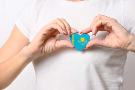 Love Kazakhstan. The girl holds a heart in the form of the flag of Kazakhstan on her chest. Kazakh patriotism concept