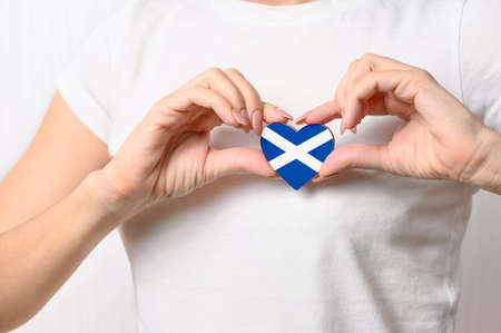 Love Scotland. The girl holds a heart in the form of the flag of Scotland on her chest. Scottish patriotism concept