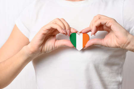Love Ireland. The girl holds a heart in the form of the flag of Ireland on her chest. Irish patriotism concept Banque d'images