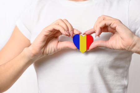 Love Romania. The girl holds a heart in the form of the flag of Romania on her chest. Romanian patriotism concept Banque d'images
