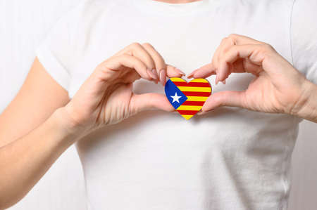 Catalan patriotism and independence concept. Love Catalonia. The girl holds a heart in the form of the unofficial flag of Catalonia (Estelada) on her chest. Blue triangle and white star on the flag. Foto de archivo
