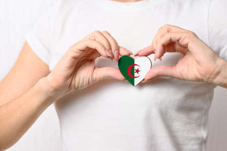 Flag of Algeria in the shape of a heart in the hands of a girl. Love Algeria. The concept of patriotism for Algerians Stock Photo