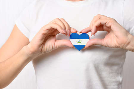 Nicaragua flag in the shape of a heart in the hands of a girl. Love Nicaragua. Patriotism Concept for Nicaragua