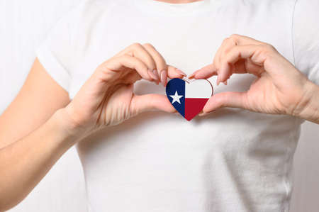 Flag of the State of Texas in the shape of a heart in the hands of a girl. Love Texas. The concept of patriotism Banque d'images