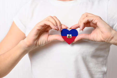 Flag of Haiti in the shape of a heart in the hands of a girl. Love Haiti. The concept of patriotism
