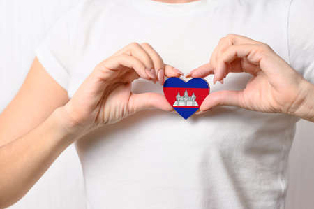 Flag of Cambodia in the shape of a heart in the hands of a girl. Love Cambodia. The concept of patriotism Cambodia