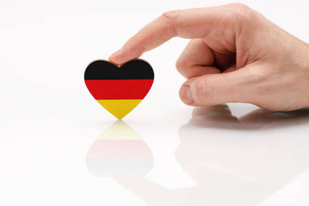 Love and respect Germany. A man's hand holds a heart in the shape of the Germany flag on a white glass surface. The concept of German patriotism and pride. Foto de archivo