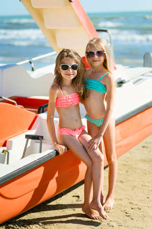 Portrait of two joyful sisters on the beach near the red boat. Two girls by the sea. Vertical frame. Foto de archivo